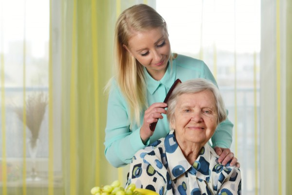 Caregiver combing loved one's hair