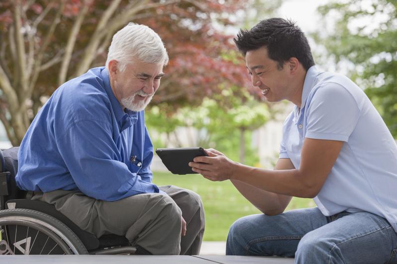 A Man Talks to a Man in a Wheelchair
