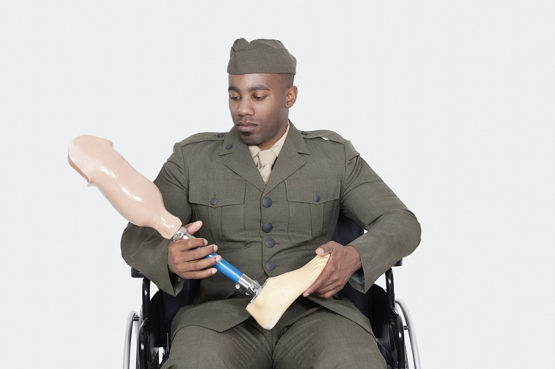 Disabled veteran holds prosthetic leg and sits in wheelchair