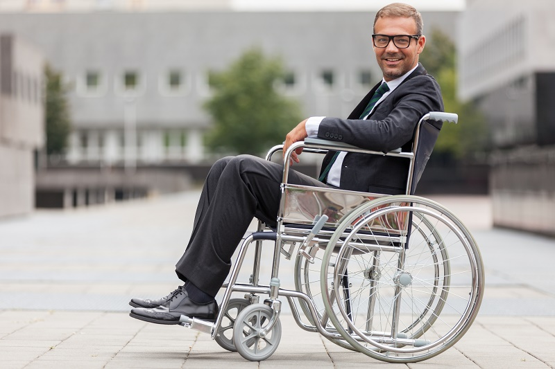 Man wearing a suit smiles while sitting in a wheelchair