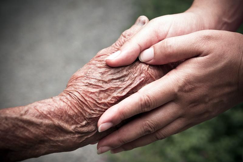 Younger hands embrace older hand.
