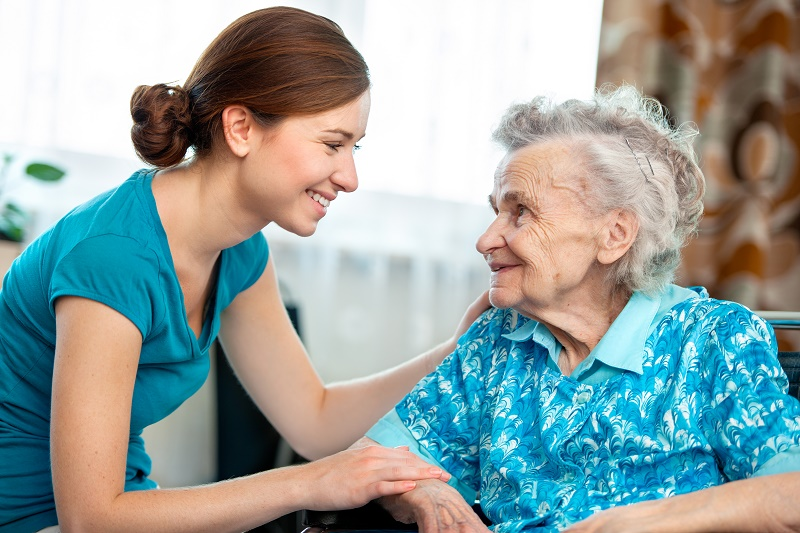 Caregiver smiles at elderly woman.