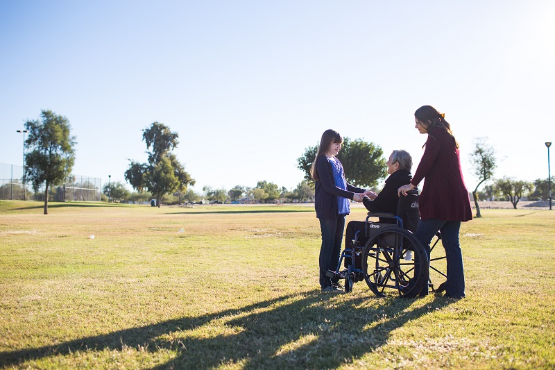 Family pushes woman in wheelchair.
