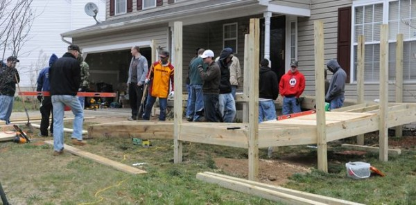 A group of people work to add a ramp to the front entrance of a house.