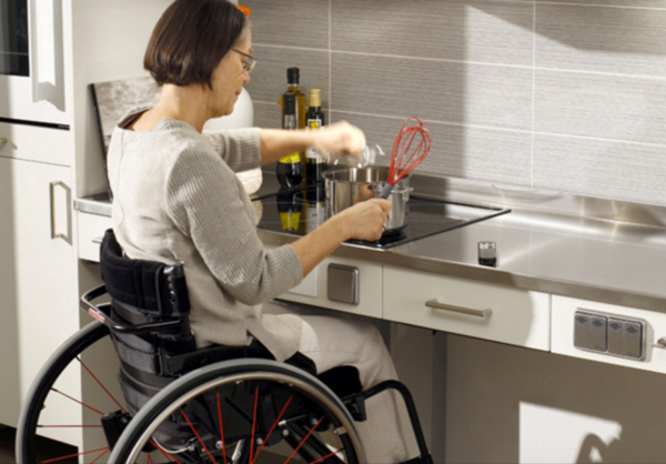 A woman in a wheelchair is able to cook at a lowered counter top.